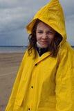一件黄色雨衣的一个美丽的女孩在雨中在春天站立在海湾的岸并且起皱纹她的鼻子 库存图片