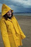 一件黄色雨衣的一个年轻美丽的女孩在雨中在春天站立在海湾的岸并且起皱纹她的鼻子 库存图片