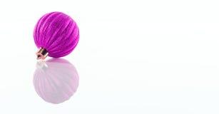 一紫色,在白色反射性有机玻璃背景隔绝的桃红色圣诞节球 库存照片