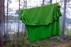一件绿色综合性T恤杉在一条绳索被烘干在树中的森林里 免版税图库摄影