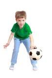 一件绿色T恤杉和牛仔裤的滑稽的逗人喜爱的小男孩 免版税库存照片