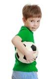 一件绿色T恤杉和牛仔裤的滑稽的逗人喜爱的小男孩 免版税库存图片