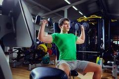 一件绿色T恤杉的肌肉人练习举重健身房 免版税库存图片