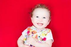 一件花卉五颜六色的礼服的笑的女婴 免版税库存图片