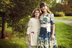 一件花服的美丽的年轻母亲和女儿青少年10 ye 免版税库存图片