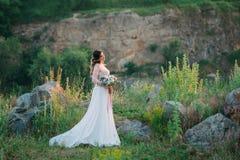 一件花梢白色礼服的美丽的夫人在pict的背景 免版税库存照片