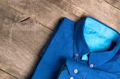 一件蓝色人衬衣在木背景 免版税库存图片