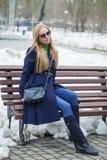 一件蓝色外套的少妇坐一条长凳在冬天公园 库存照片