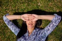 一件蓝色女衬衫的美丽的亚裔女孩在绿草说谎并且盖她的面孔用她的手 免版税库存图片