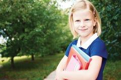 一件蓝色学校礼服的微笑的女小学生,有bo的 免版税库存照片