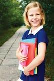 一件蓝色学校礼服的愉快的微笑的女小学生,有书的 免版税库存图片