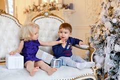 一件蓝色毛线衣和一点白肤金发的gir的小迷人的男婴 免版税图库摄影