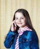 一件蓝色牛仔布夹克的女孩谈话在电话 免版税库存照片