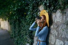一件蓝色礼服和戴的帽子年轻美丽的妇女在一条街道上的一台影片照相机做一张照片在城市 免版税库存图片