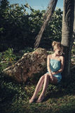 一件蓝色礼服的可爱的女孩,摆在坐在棕榈树树荫下  库存图片