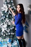 一件蓝色礼服的女孩装饰一棵圣诞树 免版税库存图片