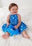 一件蓝色礼服的小女孩坐床和笑,使用与玩具 免版税库存照片