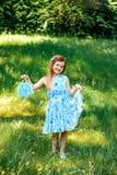 一件蓝色礼服的小女孩有一个蓝色袋子的在夏天庭院里 库存照片