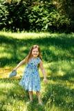 一件蓝色礼服的小女孩有一个蓝色袋子的在夏天庭院里 免版税库存图片
