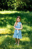 一件蓝色礼服的小女孩有一个蓝色袋子的在夏天庭院里 免版税库存照片