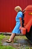 一件蓝色礼服的美丽的健康资深妇女乘一辆红色卡车 库存照片