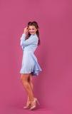 一件蓝色礼服的美丽的妇女在桃红色背景在演播室 库存图片