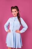 一件蓝色礼服的美丽的妇女在桃红色背景在演播室 免版税库存图片