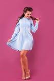 一件蓝色礼服的美丽的妇女在桃红色背景在演播室 免版税库存照片
