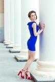 一件蓝色礼服的美丽的性感的女孩有美好的发型和构成的在镇红色鞋子的街道上站立 免版税库存照片