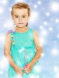 一件蓝色礼服的美丽的矮小的被晒黑的女孩 免版税库存图片