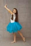 一件蓝色芭蕾舞短裙的青少年的芭蕾舞女演员有长的头发的 免版税库存图片