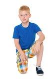 一件蓝色衬衣的小男孩坐 免版税库存图片