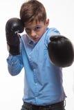 一件蓝色衬衣的情感男孩浅黑肤色的男人有拳击手套的在手上 免版税库存照片