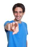 一件蓝色衬衣的笑的西班牙人指向照相机的 库存照片