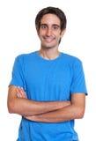 一件蓝色衬衣的笑的西班牙人有横渡的 库存图片