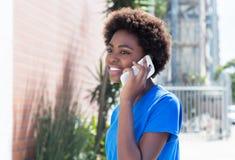一件蓝色衬衣的非裔美国人的妇女讲话在电话 库存照片