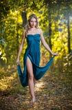 一件蓝色长的礼服的少妇在日落在森林里。 图库摄影