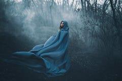 一件蓝色雨衣的一名大,美丽的妇女 免版税库存照片