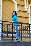 一件蓝色高领衫的美丽的女孩在栏杆附近 免版税库存图片