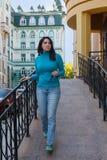 一件蓝色高领衫的美丽的女孩在栏杆附近 库存图片