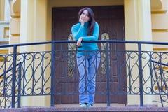 一件蓝色高领衫的美丽的女孩在栏杆附近 免版税库存照片