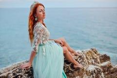 一件薄荷的礼服的一个少妇坐在亚得里亚海的岸的一块大石头 库存照片