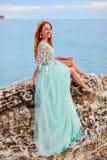 一件薄荷的礼服的一个少妇坐在亚得里亚海的岸的一块大石头 免版税库存图片