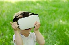 一件虚拟现实盔甲的小男孩在绿草背景  免版税库存图片