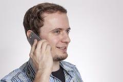 一件衬衣的人有对您的耳朵的电话的 免版税库存照片
