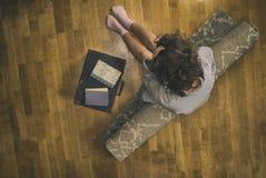 一件衬衣的美丽的少妇在带着手提箱的一个地毯 库存照片