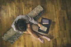 一件衬衣的美丽的少妇在带着手提箱的一个地毯 免版税库存照片