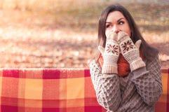 一件被编织的毛线衣和手套的年轻美丽的惊奇的妇女 图库摄影