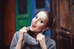 一件被编织的高领衫毛线衣的少妇微笑和看照相机的 接近的纵向 库存图片