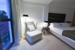 一间豪华旅馆卧室的内部在晚上 免版税库存图片